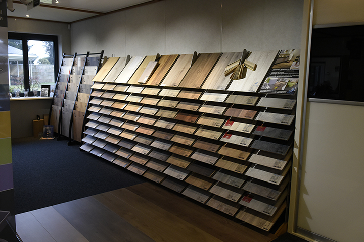 Laminaatvloeren - Overzicht van laminaatplanken (ook waterbestendige laminaatdelen) en tegelmotief in de showroom
