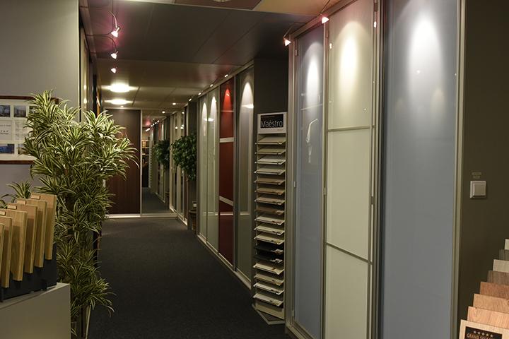 Schuifwandkast - New IPD kasten - Blauw lakglasdeuren met tussentrims voor de vakverdeling en boogspots/pendelspots inclusief afstandsbediening